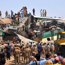 Soldiers and volunteers work at the site of a train collision in the Ghotki district of southern Pakistan, Monday, June 7, 2021. Two express trains collided early Monday, killing dozens of passengers authorities said, as rescuers and villagers worked to pull injured people and more bodies from the wreckage. (AP Photo/Waleed Saddique)