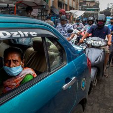 Commuters wearing face masks cross a market area on foot and in vehicles during a partial relaxation of restrictions to curb the spread of coronavirus in Gauhati, India, Wednesday, June 9, 2021. (AP Photo/Anupam Nath)
