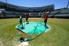 The grounds crew prepares The Ballpark at Jackson before a home game for the Winnipeg Goldeyes of the American Association, Tuesday, June 22, 2021, in Jackson, Tenn. When Major League Baseball stripped 40 teams of their affiliation in a drastic shakeup of the minor leagues this winter, Jackson lost the Jackson Generals, the Double-A affiliate of the Arizona Diamondbacks. The Goldeyes are playing their home games in Jackson due to COVID-19 restrictions. (AP Photo/Mark Humphrey)