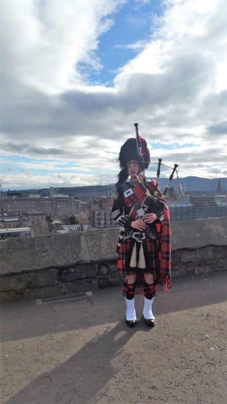 Scottish man with bagpipe outside the Edinburgh Castle. Scotland