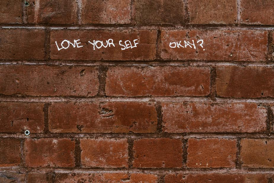 Love yourself message on the wall, self-esteem, life