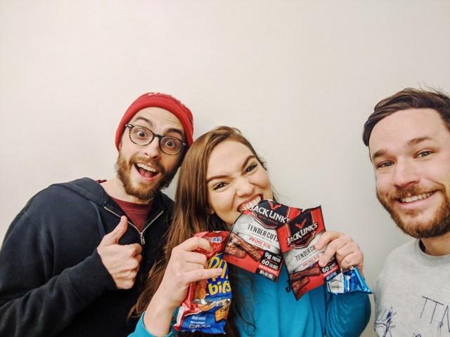 Evan Forde Barden, Addie Weyrich, and Patrick Cartelli taking a selfie. Addie is holding packs of beef jerky.