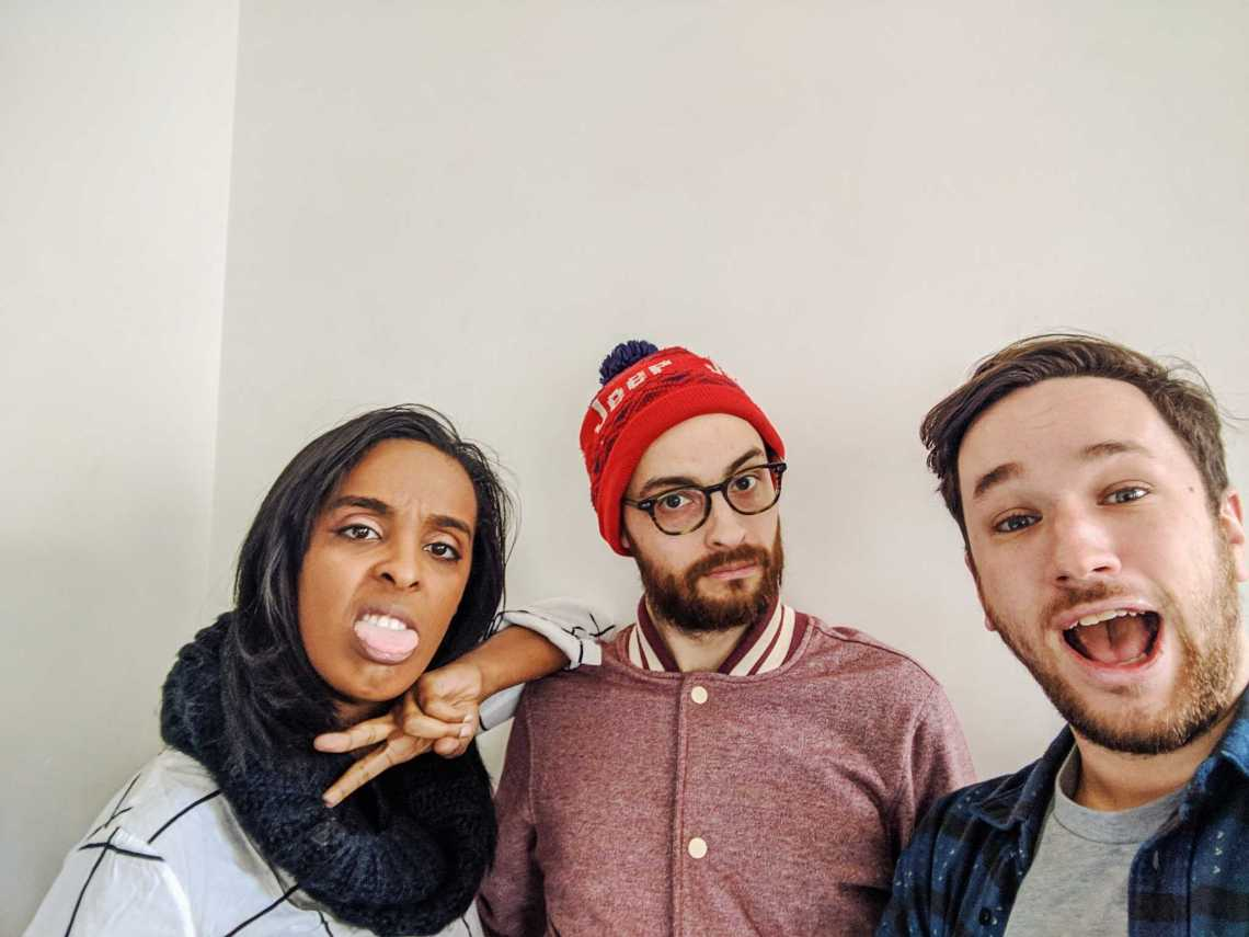 Corin Wells, giving a peace sign and sticking her tongue out, next to Evan Barden and Pat Cartelli, mouth agape