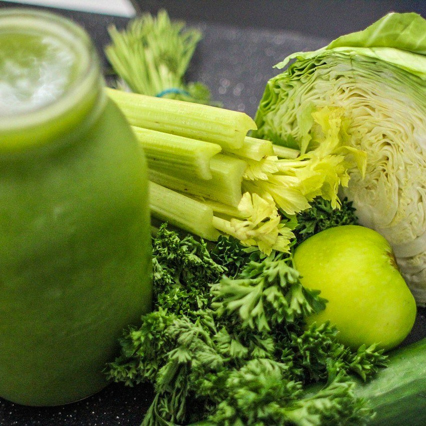 Image of a jar of green juice next to green cabbage, celery, parsley, cucumber, and an apple