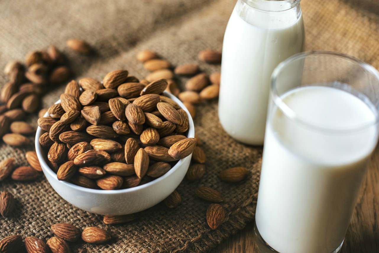 An image of two glasses of almond milk and a bowl of almonds