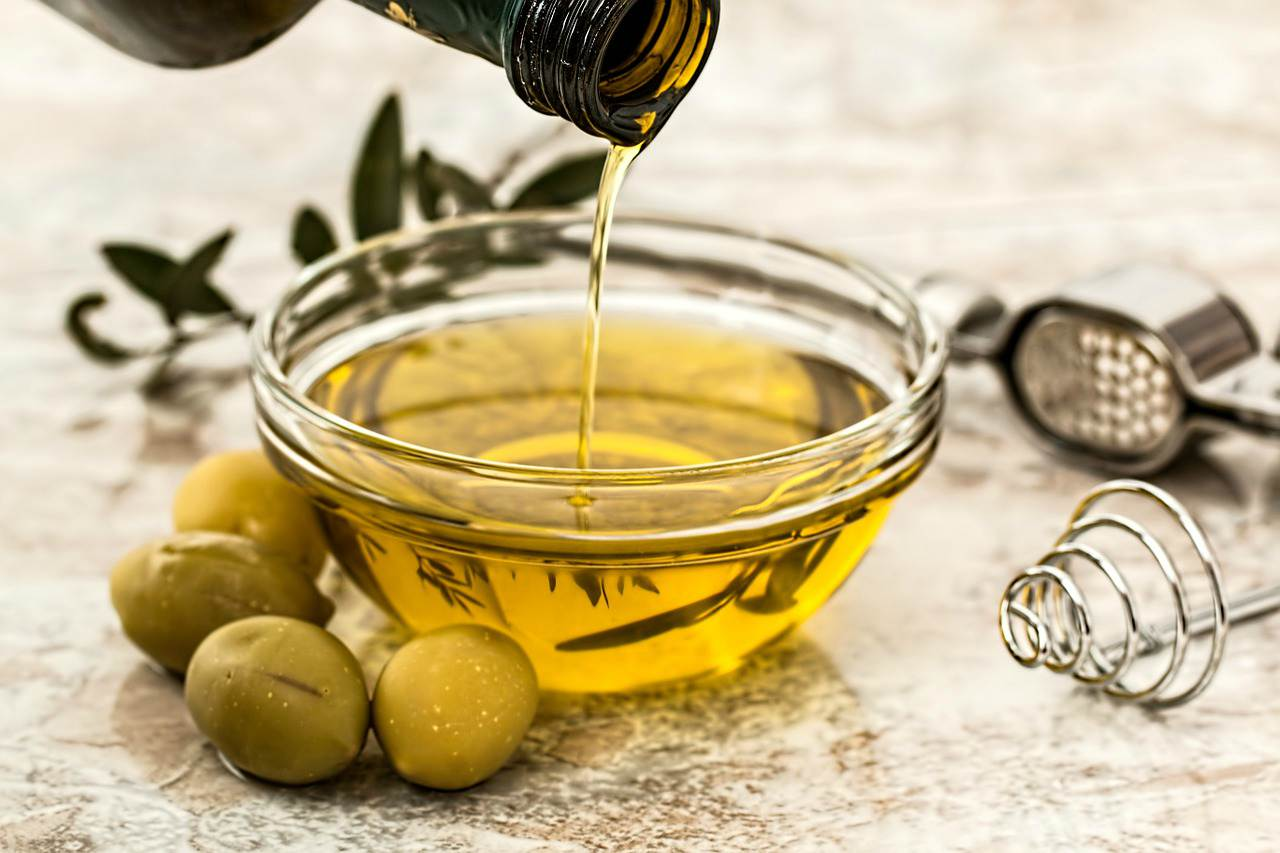 An image of olive oil being poured from a bottle into a small bowl