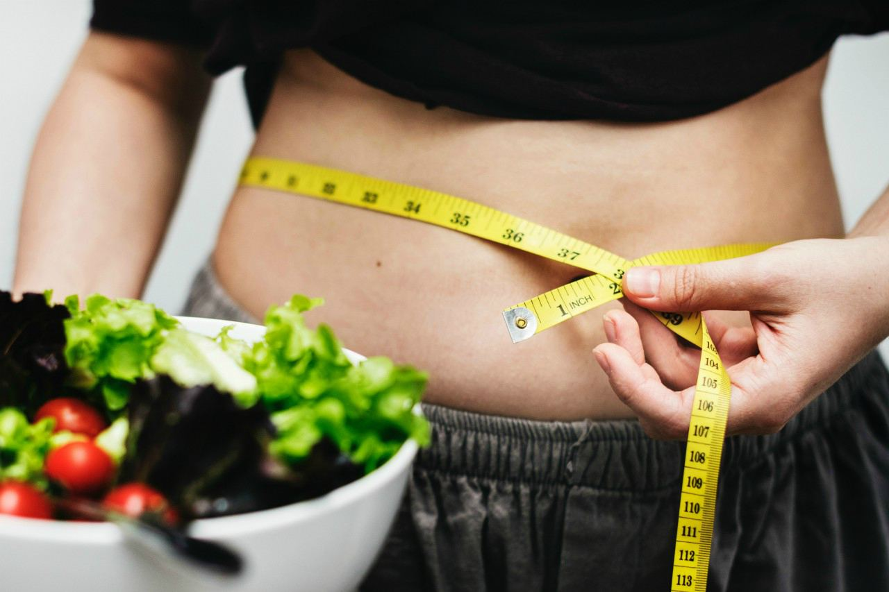 An image of a woman measuring her waist while holding a bowl full of salad