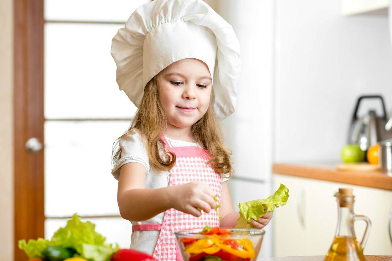 An image of a young girl tearing lettuce to put in a bowl of salad