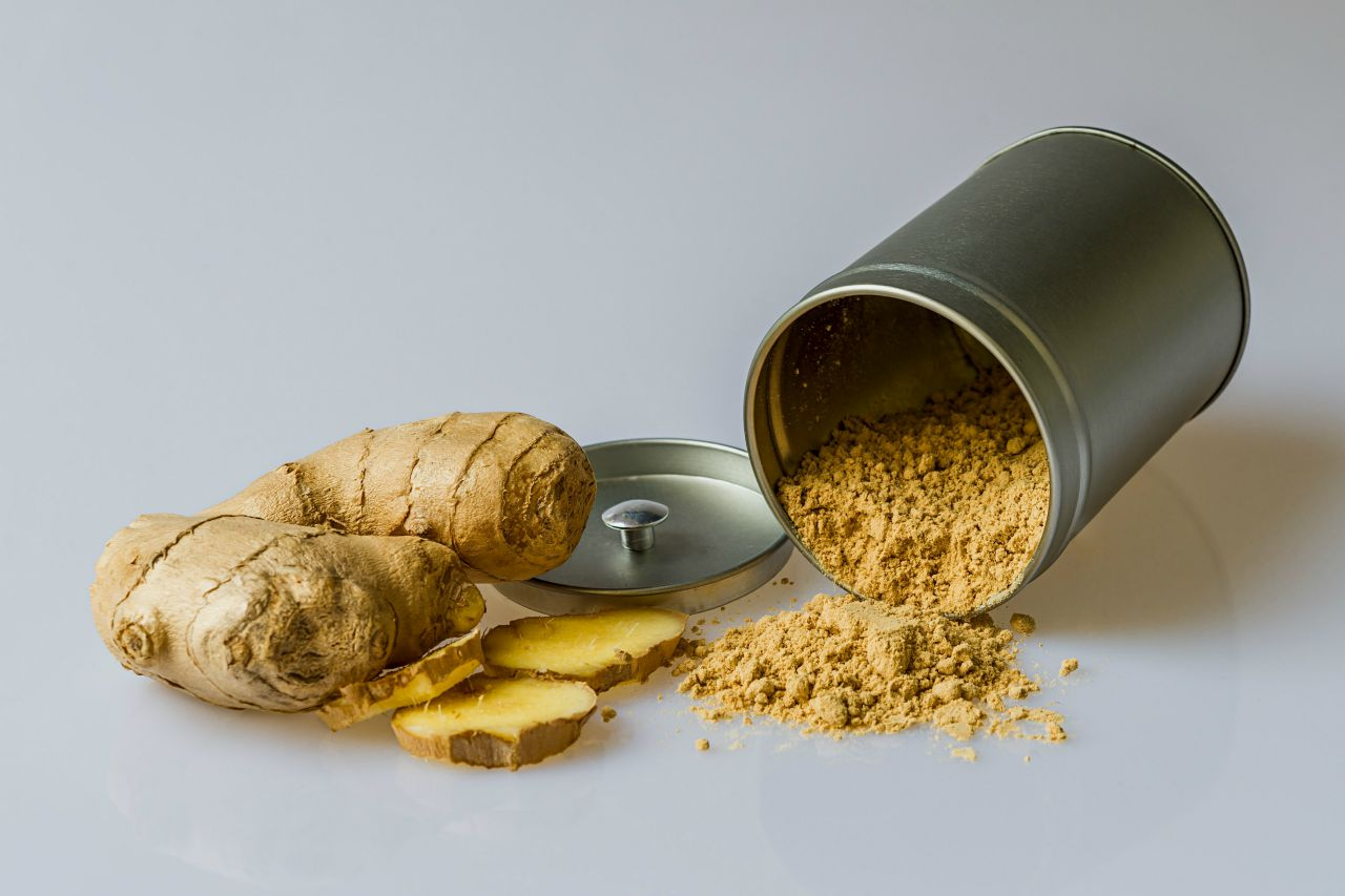 An image of fresh ginger root next to a tin spilling ginger powder
