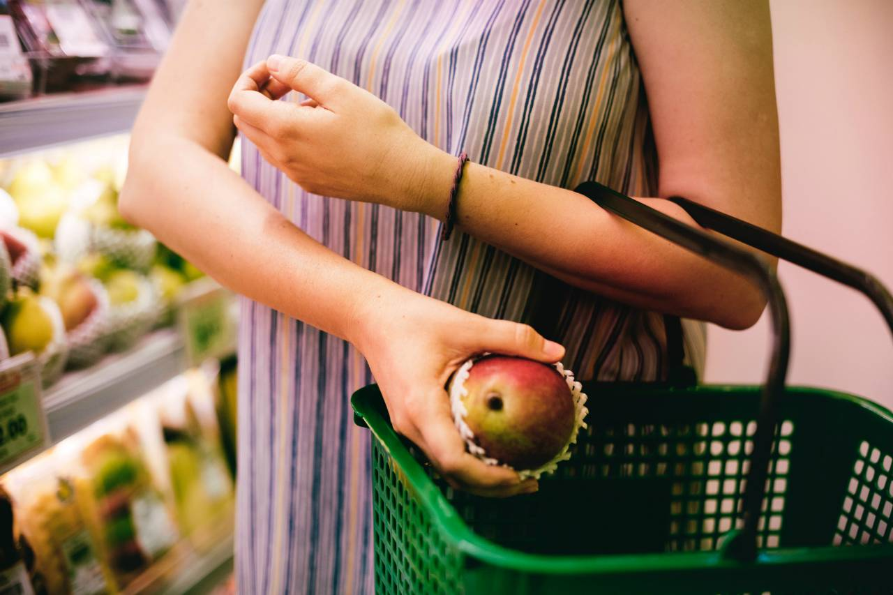 An image of a woman putting a mango into a shopping basket
