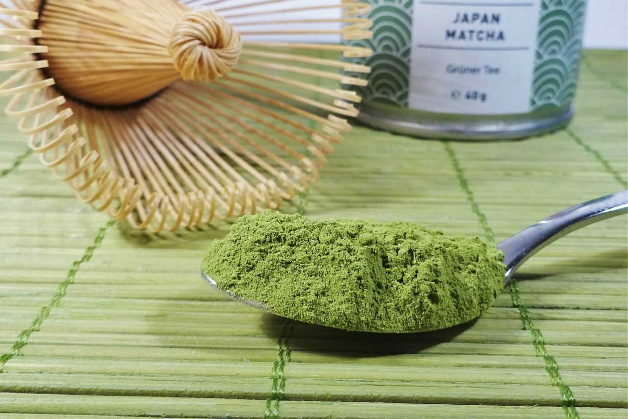 An image of matcha green tea powder on a spoon