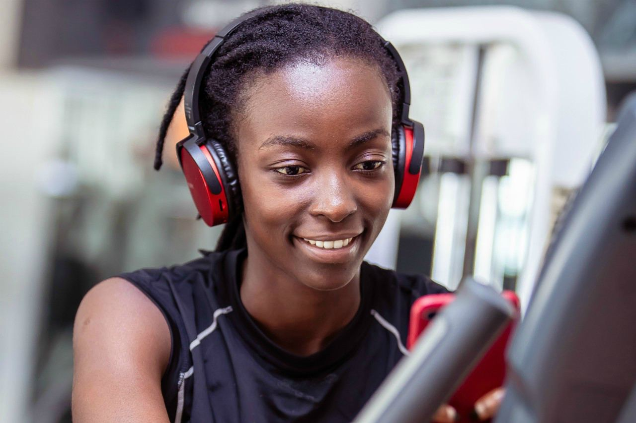An image of a woman on an exercise machine at the gym wearing headphones and listening to music