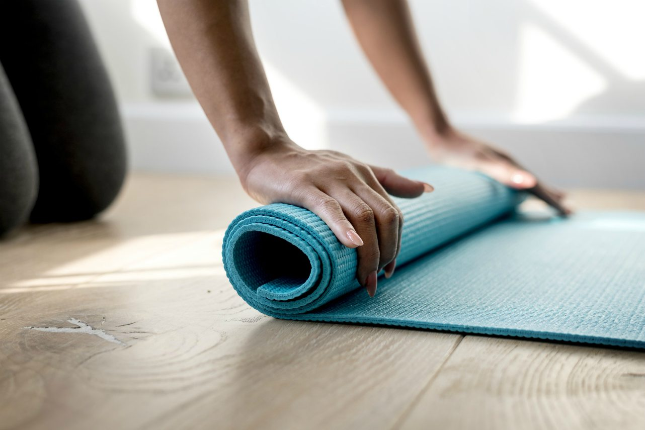 An image of a woman rolling up a yoga mat