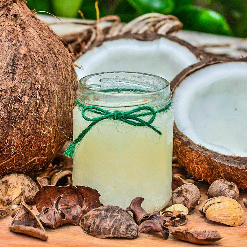 An image of a glass jar containing coconut water surrounded by fresh coconuts