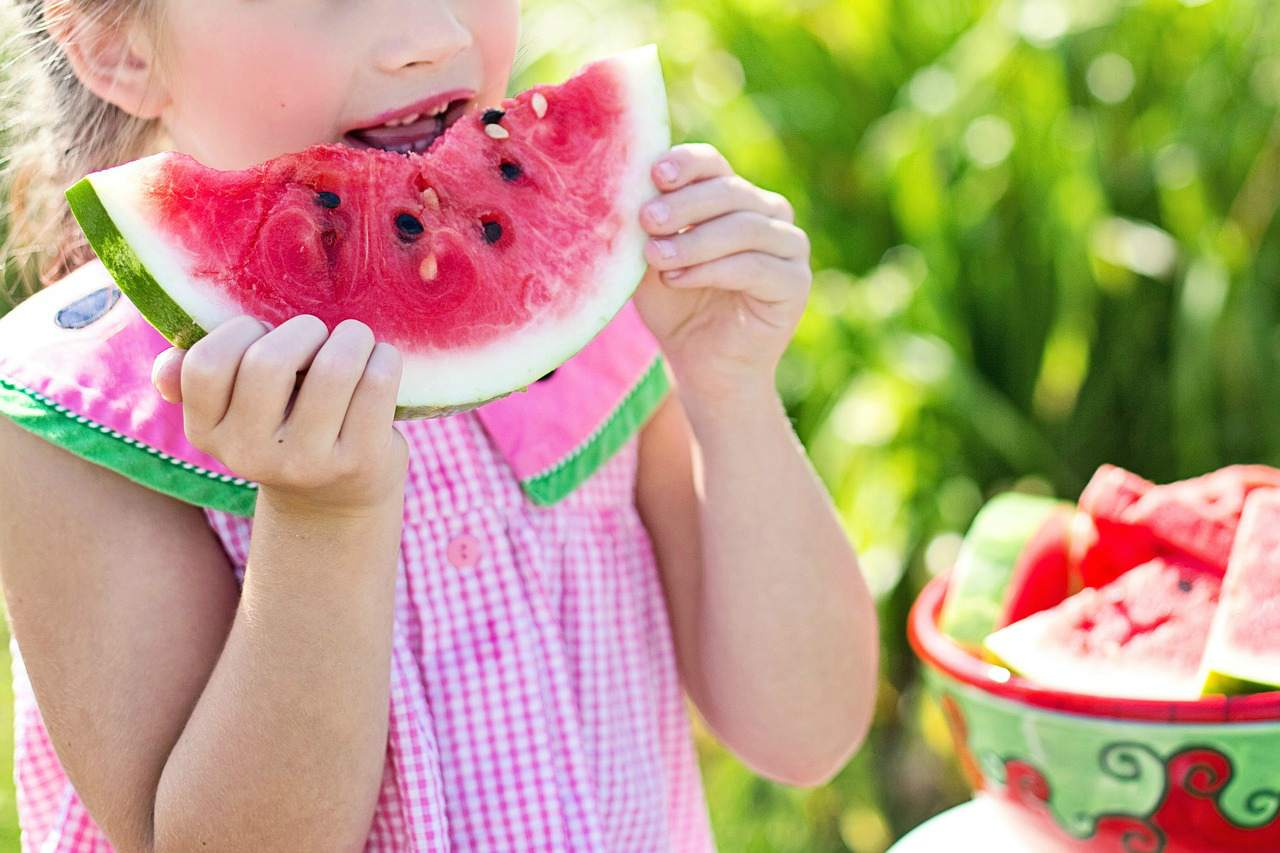 An image of a girl eating watermelon