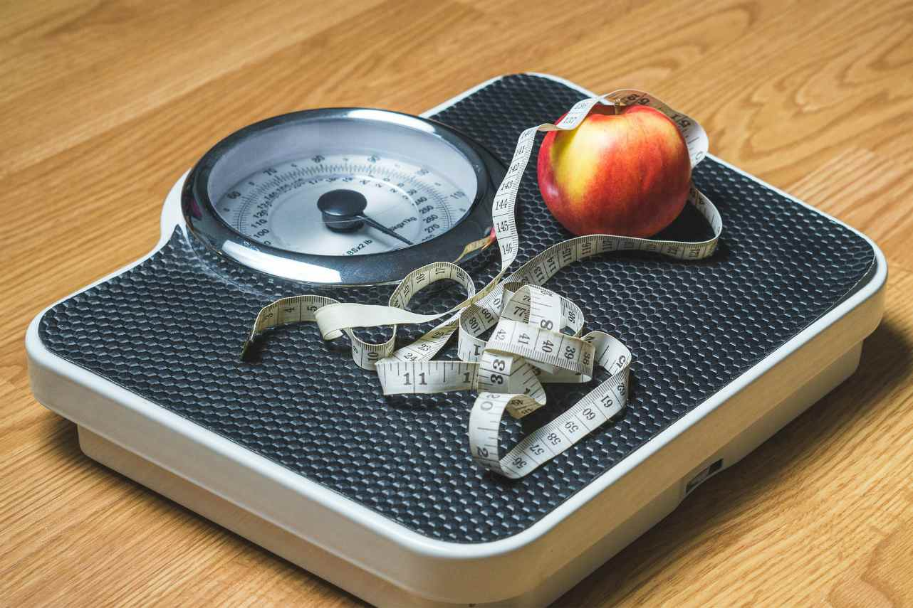 An image of bathroom scales with a tapemeasure and an apple on top