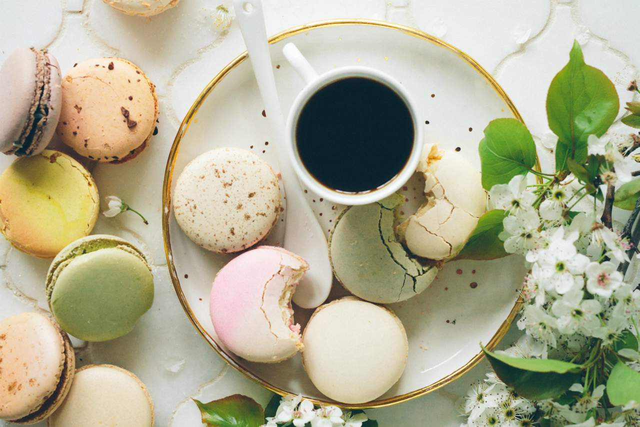 An image of a cup of black coffee surrounded by macaroons