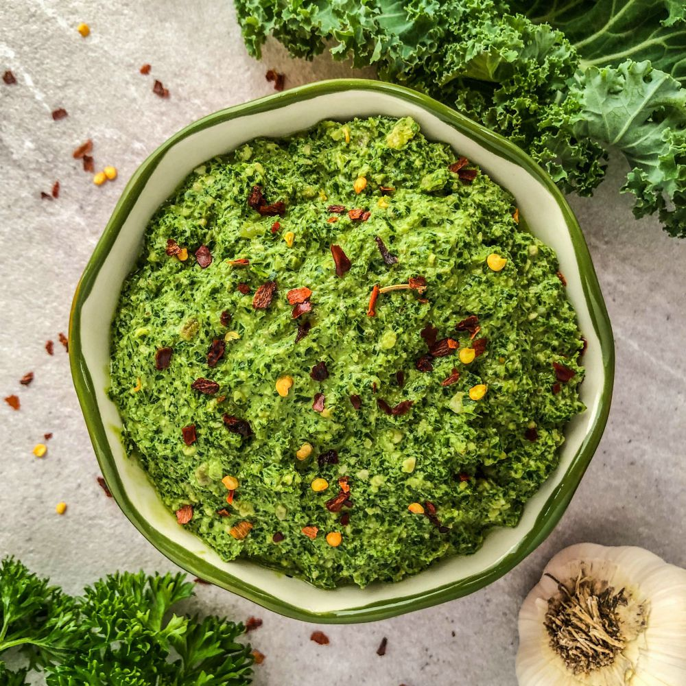 An image of a bowl of kale & parsley pesto with fresh garlic, kale, and parsley next to it.