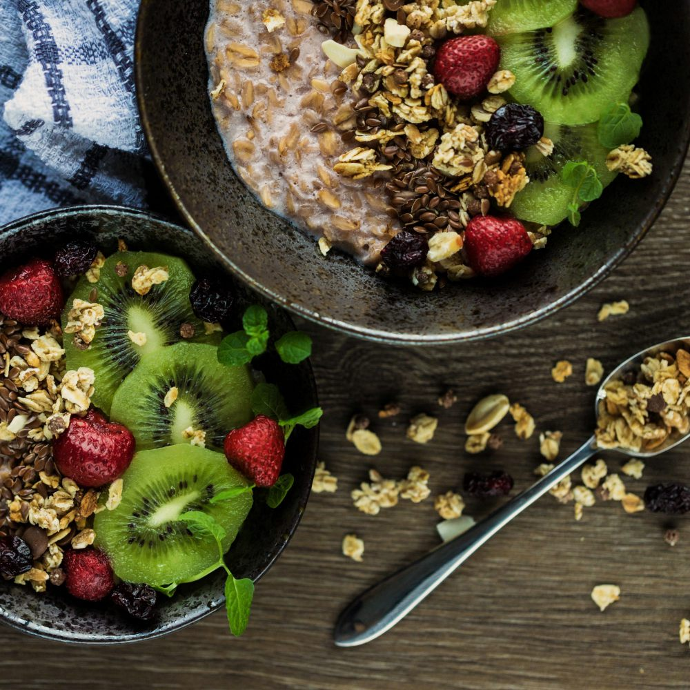 An image of two bowls with oats, flax, berries, and sliced kiwi.