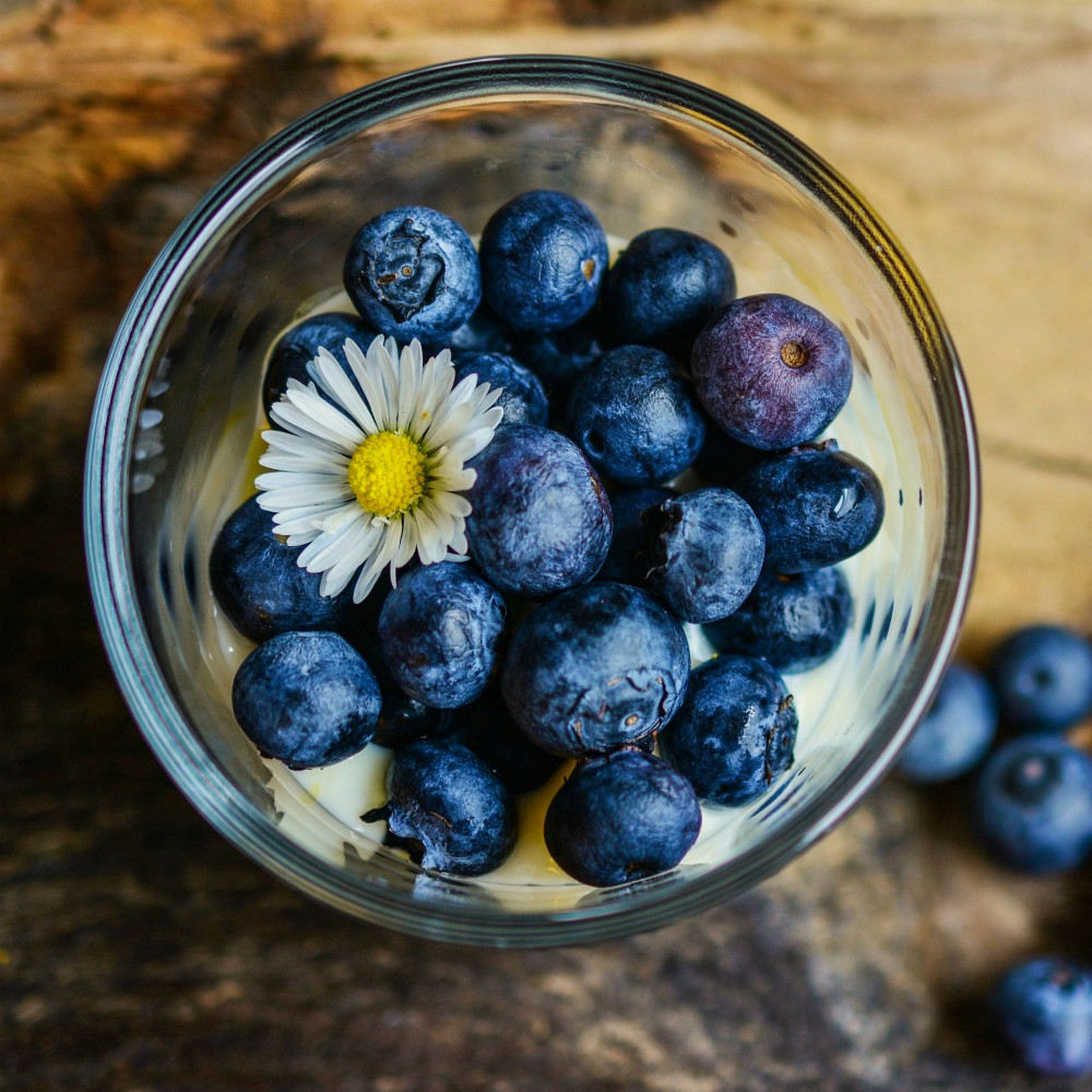 An image of a glass with blueberries in it.