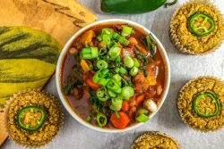 An image of a bowl of Three Bean Vegetable Chili and Jalapeño Cornbread Muffins.