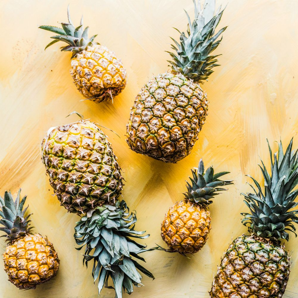 An image of various sized pineapples on a yellow background.