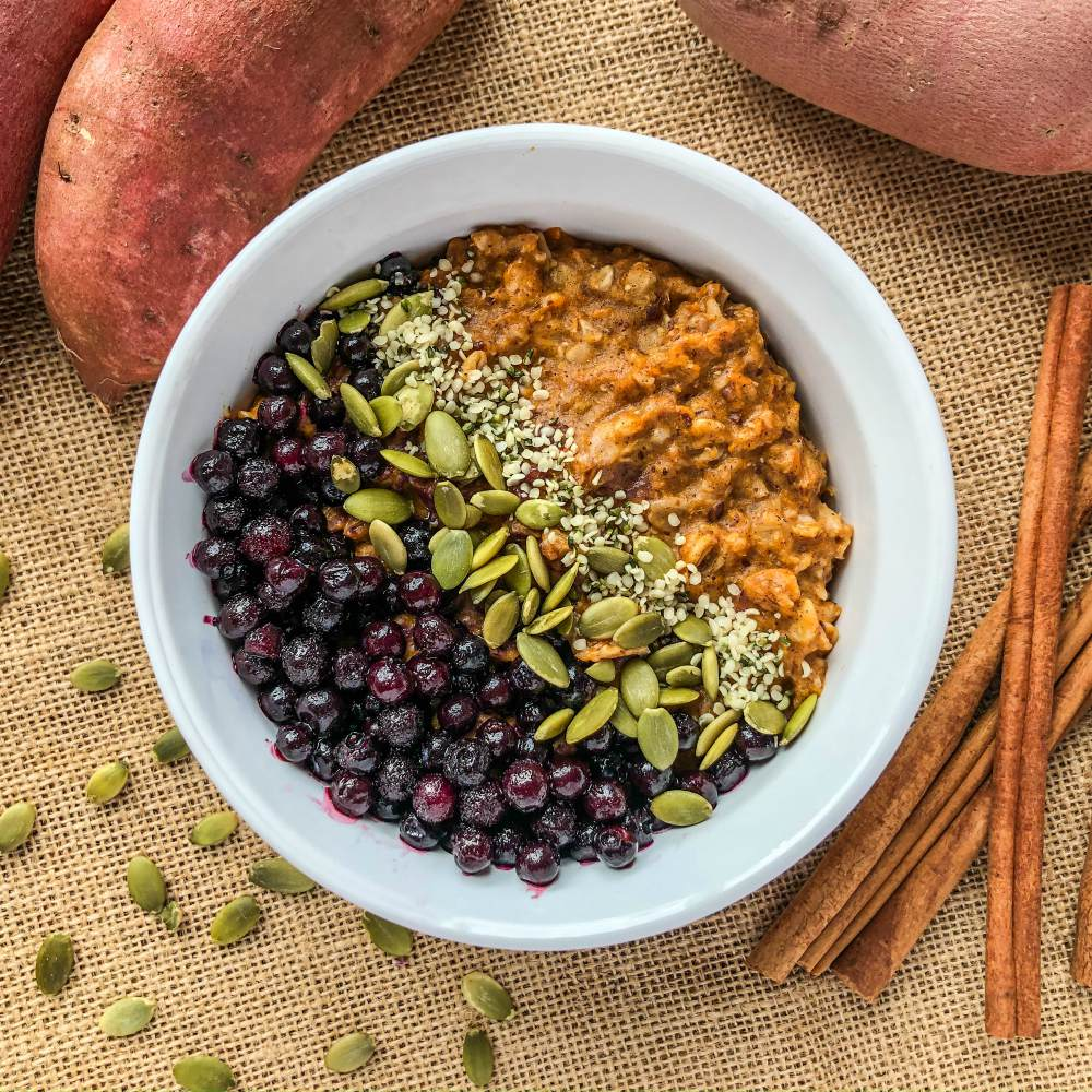 An image of a bowl of sweet potato oatmeal topped with blueberries, pumpkin seeds, and hemp seeds.