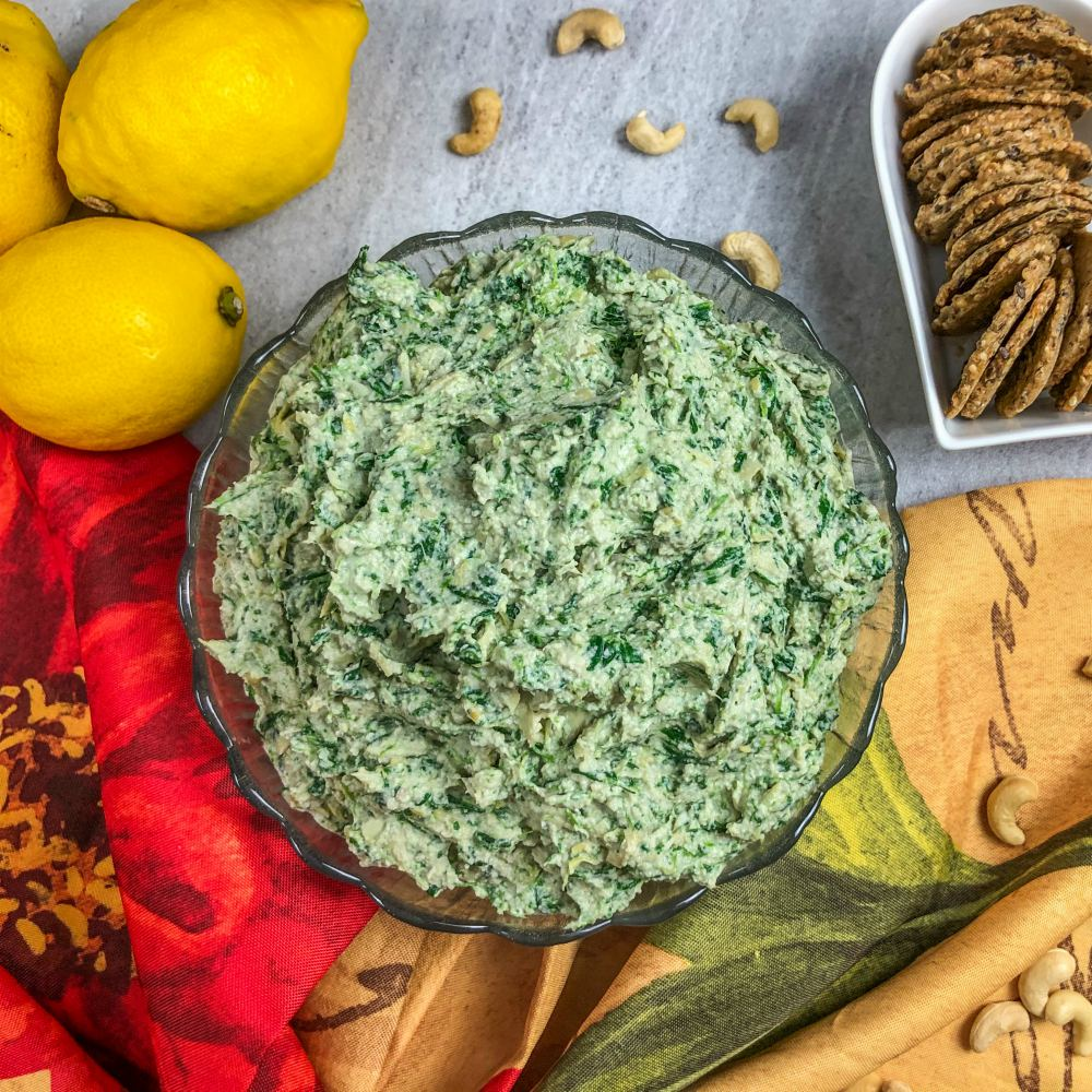 An image of a bowl of spinach & artichoke dip, lemons, and a bowl of crackers.