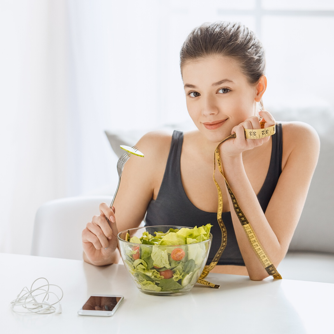 An image of a woman eating a fresh salad.