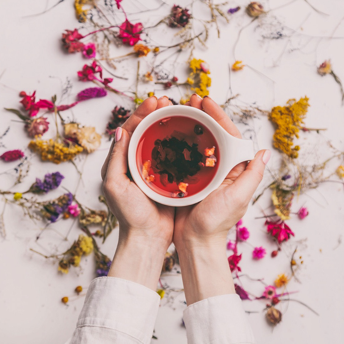 An image of a woman hands holding a cup of tea surrounded by dried flowers.