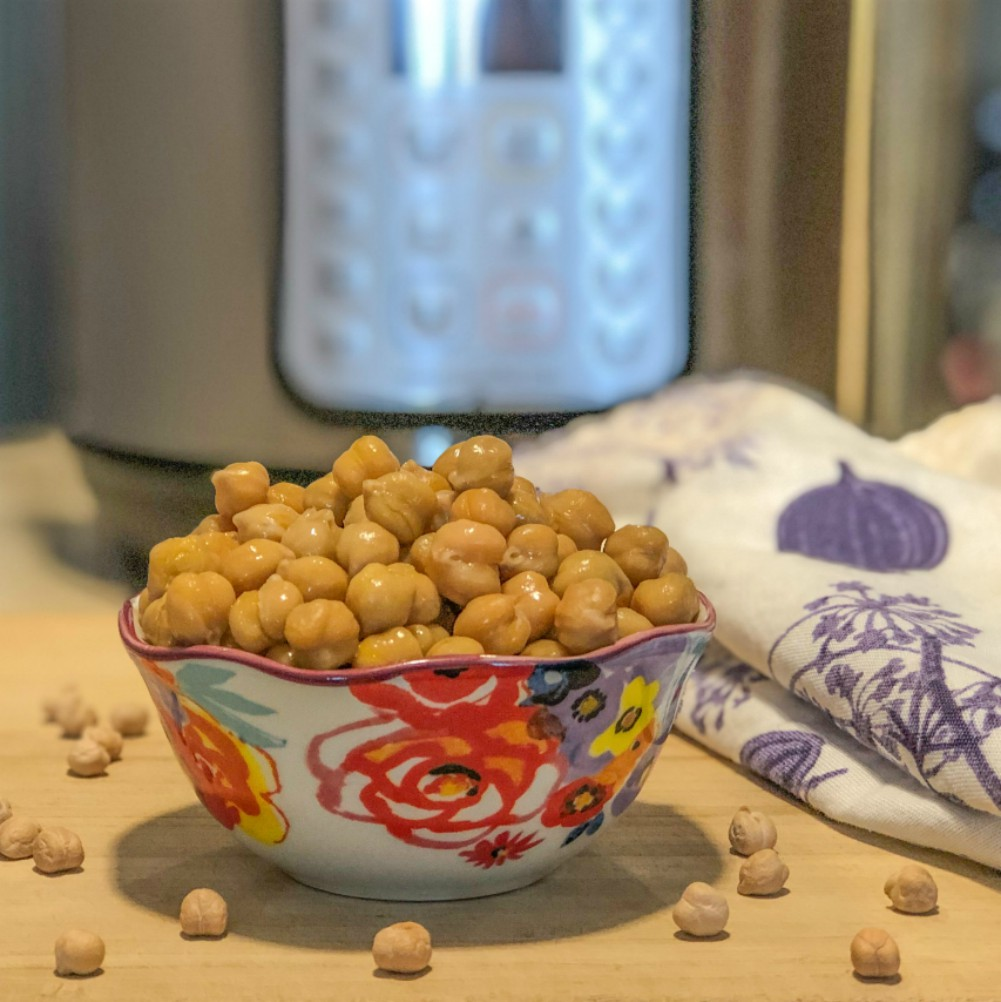 An image of a bowl of cooked chickpeas in front of an instant pot.