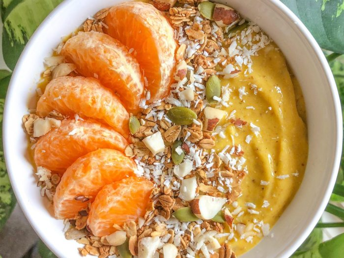 An image of a mango smoothie bowl topped with granola and mandarin segments.
