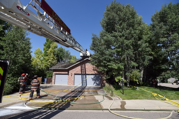 LOVELAND, CO-July 5, 2019: Loveland Fire Rescue Authority firefighters use the ladder on their tower truck while fighting a house fire at 3079 Kiowa Dr., Friday, July 5, 2019, in west Loveland. (Jenny Sparks / Loveland Reporter-Herald)