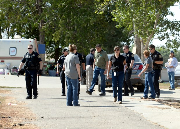 Larimer County Sheriff's deputies and code enforcement employees, including Code Enforcement Compliance Officer Tony Brooks, center, get ready to leave a property at 860 Fourth St. SE on Wednesday after informing the owner that he was not complying with a court order that states people are not allowed to camp there. (Jenny Sparks/Loveland Reporter-Herald)