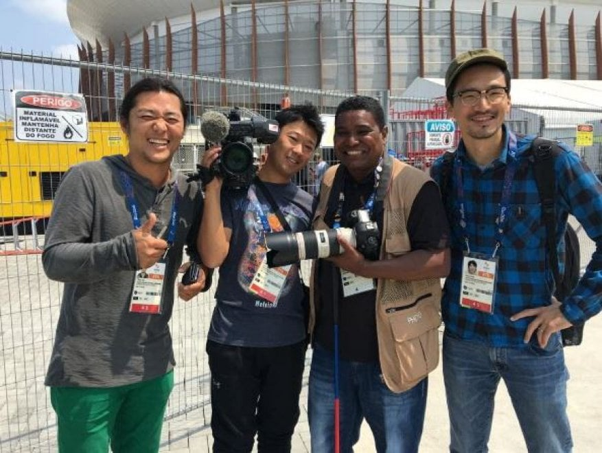Equipe da TV asahi. Testuya hirano joao kume ,em segundo plano as grades e arenas na cor branca.