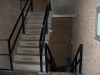 Photograph of a narrow, fire-escape stairwell in Stokely ...