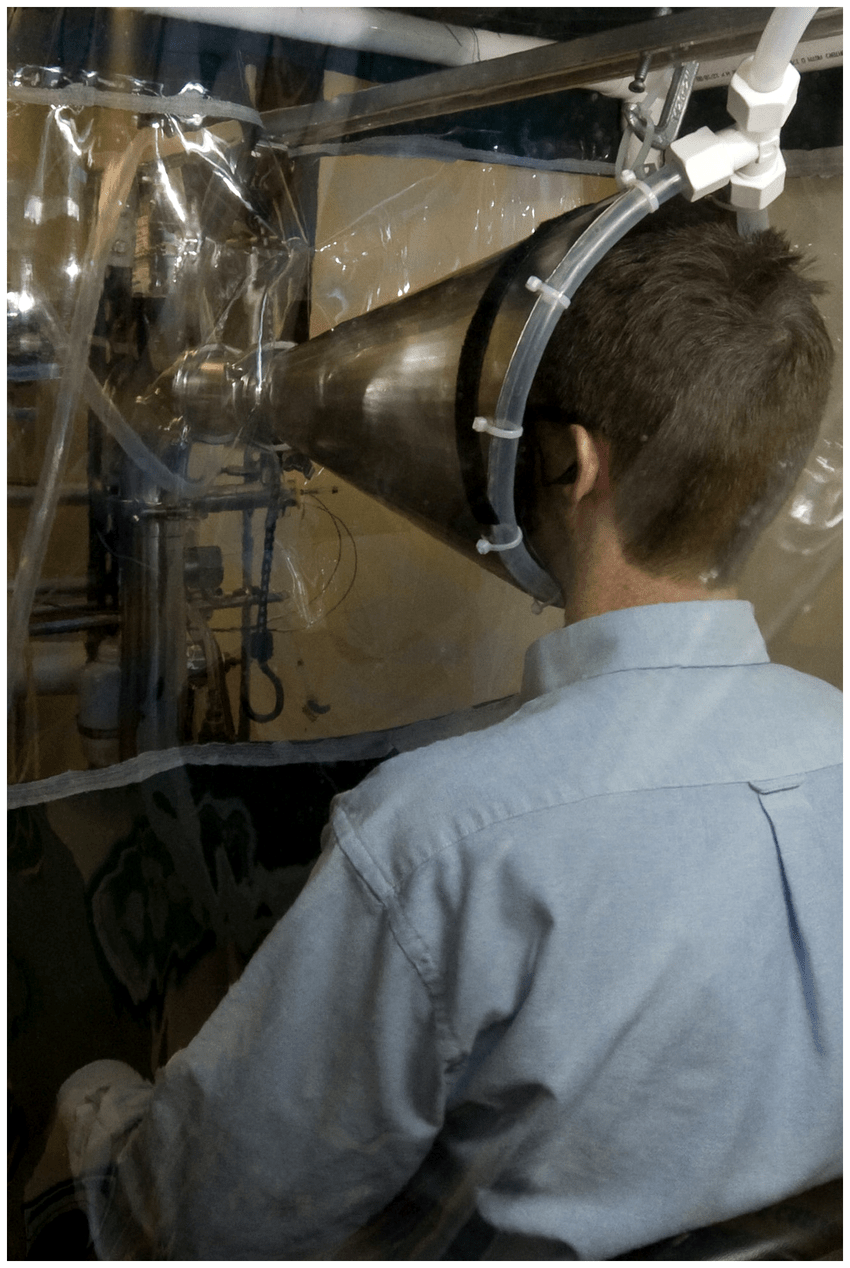 hight resolution of each volunteer sat as shown with face inside the inlet cone of the human exhaled breath air sampler inside a booth supplied with hepa filtered