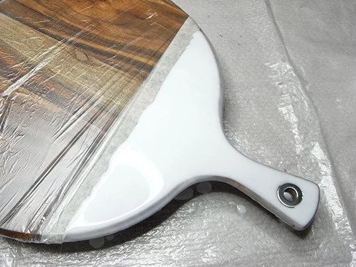 white layer of resin on cheese board handles