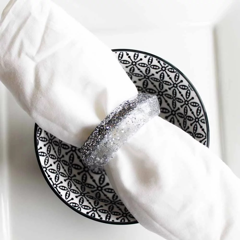 silver glitter resin napkin rings silver on black and white dish