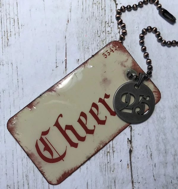 tag 5 - Flashcard by Tim Holtz with distressed edges, charm, and chain