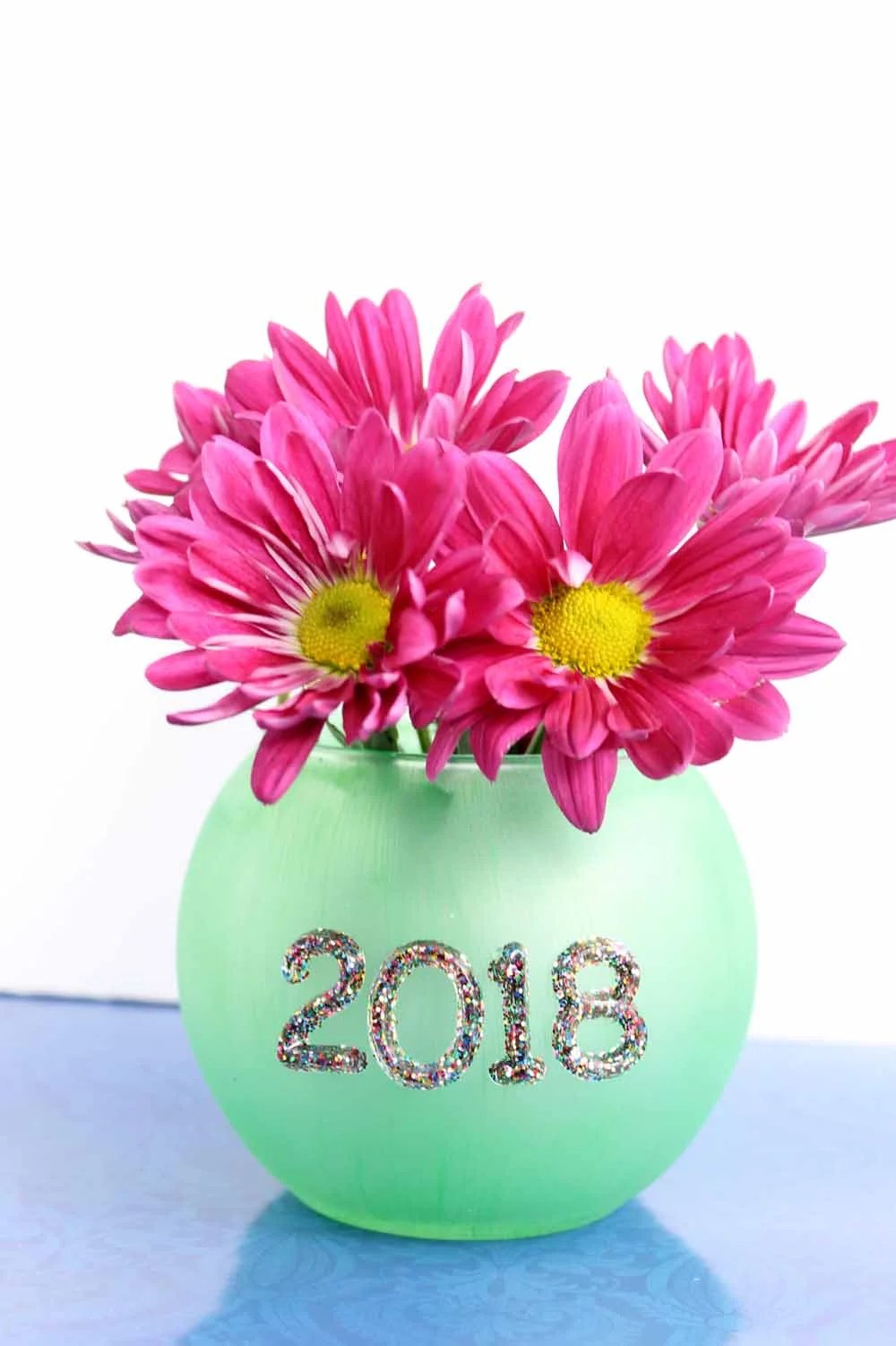 pink flowers inside green glass sphere-shaped vase with multi-color glitter resin numbers that say 2018
