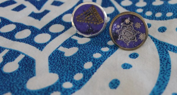 Front view of two rings with gold mandala designs on deep purple resin background