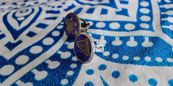 Side view of rings with gold mandala designs on deep purple resin background