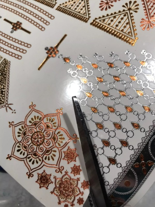 Cutting out gold mandala temporary tattoos to make ring