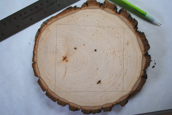 slice of wood with measurements for cutting drawn on and a ruler and a pencil