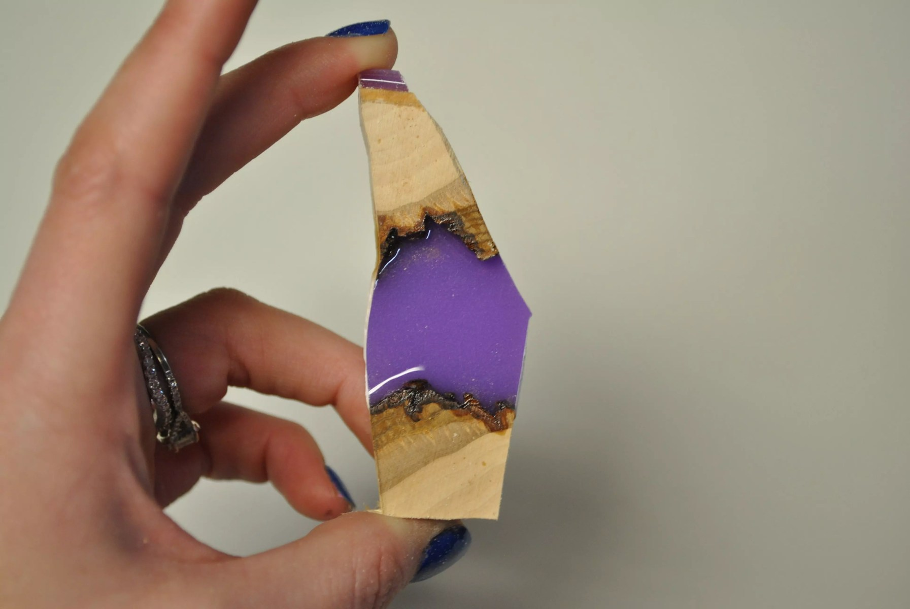left hand holding up wood and lavender resin shard