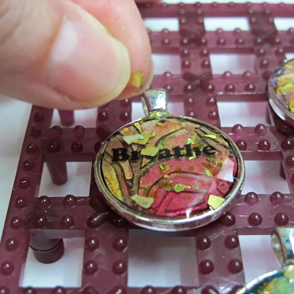 Applying glitter to resin pendant