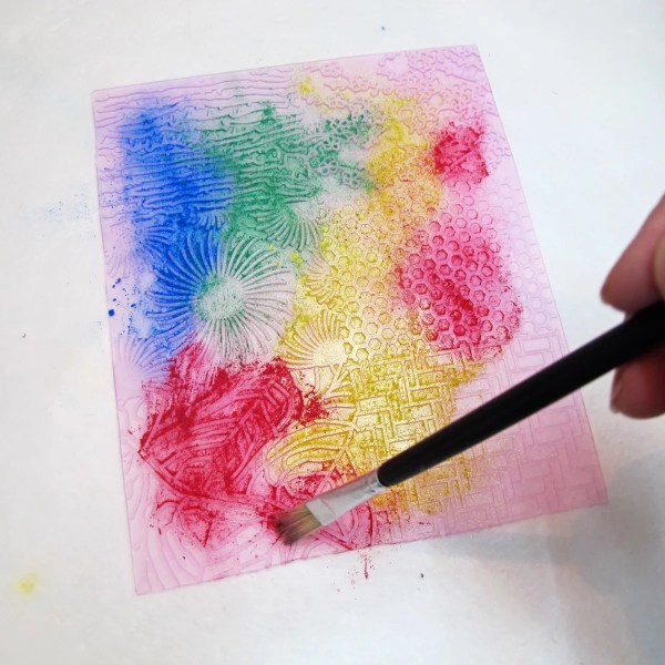 applying Pearl Ex powders to a rubber stamp surface