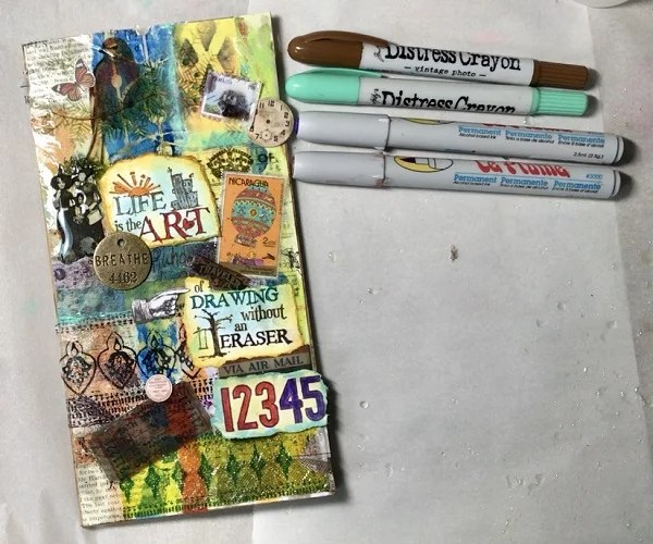 ephemera and marker added to resin art journal cover