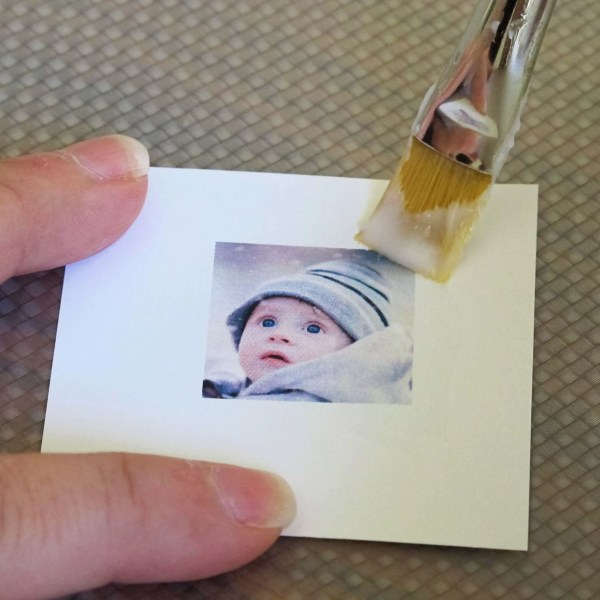 applying a layer of white glue to a photo